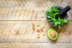 Fresh herbs, avocado and mortar on wooden background top view Royalty Free Stock Images