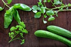 Fresh herbs on dark wood background. Fresh herbs and mini cucumbers on dark wood background in horizontal format Royalty Free Stock Photography