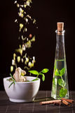 Fresh herbs falling down into the white mortar royalty free stock image