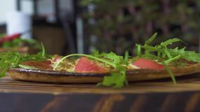 Fresh herbs falling on hot italian pizza slow motion. Close up pizza with fresh herbs in pizzeria. Food seasoning. Concept. Cooking traditional food. National stock footage
