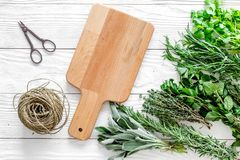 Fresh herbs and greenery for spices and cooking on white wooden desk background top view mock up Royalty Free Stock Photo