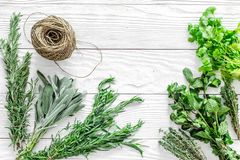 Fresh herbs and greenery for spices and cooking on white wooden desk background top view mock up Stock Photos