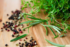 Fresh herbs and peppercorns. On kitchen table Stock Images