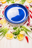 Fresh herbs and spices around blue empty plate Royalty Free Stock Photography