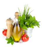 Fresh herbs, tomato, olive oil and pepper shaker Royalty Free Stock Images