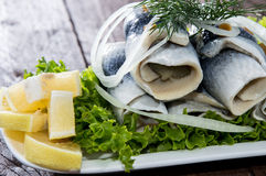 Fresh Herring Filet on a plate. Against wooden background Royalty Free Stock Images