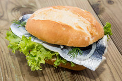 Fresh Herring on a roll (wooden background) Royalty Free Stock Image
