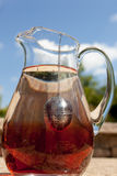 Fresh hibiscus sun tea. A glass pitcher stands against a blue sky with infused a rich red hibiscus sun tea brewing on a hot summers day. Red, white and blue Royalty Free Stock Image