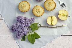 Fresh home made apple pies with apple. Fresh home made apple pies with fresh apple and lilac flowers on the blue background Royalty Free Stock Image