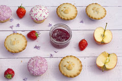 Fresh home made apple pies and cupcakes with raspberry jam. And fresh strawberries Stock Photos