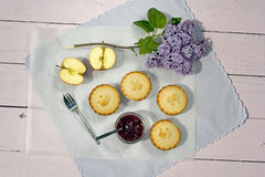 Fresh home made apple pies with fresh apple and raspberry jam. Fresh home made apple pies with fresh apple, raspberry jam and lilac flowers Stock Photos