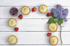Fresh home made apple pies with raspberry jam and lilac flowers. With empty space Royalty Free Stock Image