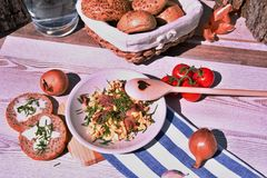 Fresh home-made breakfast eggs, onion and fried ham, set on a wooden table stock image