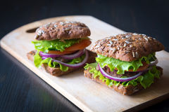 Fresh home made burgers with grain bread on wooden background Stock Photo
