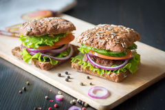 Fresh home made burgers with grain bread on wooden background Royalty Free Stock Photos