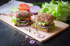 Fresh home made burgers with grain bread on wooden background Stock Photos