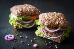 Fresh home made burgers with grain bread on wooden background Stock Image