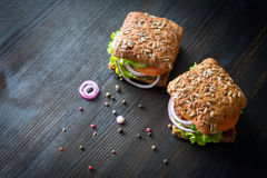 Fresh home made burgers with grain bread on wooden background Royalty Free Stock Images