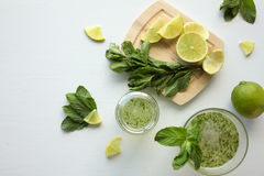 Fresh home-made lemonade with lemon, lime and mint in a glass on white background and ingredients laying on the table. (lemon, lemonade, lime, mineral, mint stock images
