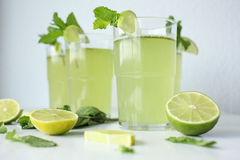 Fresh home-made lemonade with lemon, lime and mint in a glass on white background and ingredients laying on the table. (beverage, citrus, cocktail, cold, cool royalty free stock photo