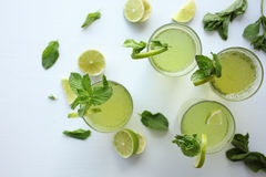 Fresh home-made lemonade with lemon, lime and mint in a glass on white background and ingredients laying on the table. (beverage, citrus, fresh, healthy, lemon royalty free stock image
