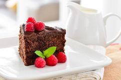 Fresh home made sticky chocolate fudge cake with raspberries Royalty Free Stock Images