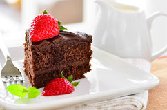 Fresh home made sticky chocolate fudge cake with strawberries Stock Image