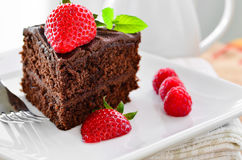 Fresh home made sticky chocolate fudge cake with strawberries and raspberries Royalty Free Stock Images