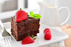Fresh home made sticky chocolate fudge cake with strawberries and raspberries Stock Photo