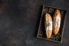 Bread with rosemary. Fresh homemade artisan bread with rosemary on rustic background, top view, copy space. Sourdough mini baguette bread royalty free stock images