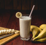 Fresh homemade banana smoothie, cutting board and bananas on dark rustic wood Stock Images