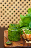 Fresh homemade Basil pesto with pine nuts in a glass jar , Basil leaf and toast on the table Stock Photography