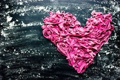 Fresh homemade beet pasta tagliatelle shaped heart on black back Stock Images