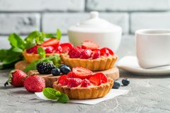Fresh homemade berrie tarts. With blueberries, blackberry and strawberries on gray background stock photo