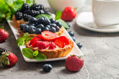 Fresh homemade berrie tarts. With blueberries, blackberry and strawberries on gray background stock photos