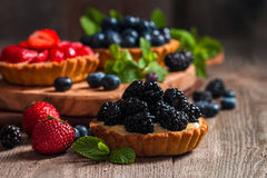 Fresh homemade berrie tarts. With blueberries, blackberry and strawberries on wooden background royalty free stock images