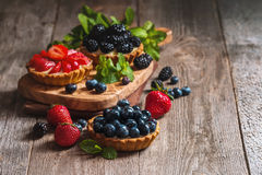 Fresh homemade berrie tarts. With blueberries, blackberry and strawberries on wooden background royalty free stock photography