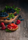Fresh homemade berrie tarts. With blueberries, blackberry and strawberries on wooden background royalty free stock photos