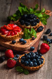 Fresh homemade berrie tarts. With blueberries, blackberry and strawberries on wooden background stock images