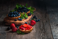 Fresh homemade berrie tarts. With blueberries, blackberry and strawberries on wooden background royalty free stock image