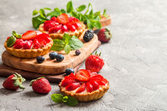 Fresh homemade berrie tarts. Fresh homemade strawberries tarts on gray background royalty free stock photos