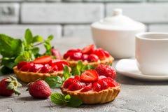Fresh homemade berrie tarts. Fresh homemade strawberries tarts on gray background royalty free stock images