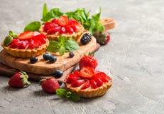 Fresh homemade berrie tarts. Fresh homemade strawberries tarts on gray background royalty free stock photo