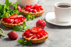 Fresh homemade berrie tarts. Fresh homemade strawberries tarts on gray background stock image