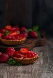 Fresh homemade berrie tarts. Fresh homemade strawberries tarts on wooden background royalty free stock images