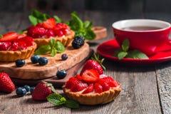 Fresh homemade berrie tarts. Fresh homemade strawberries tarts on wooden background royalty free stock photo