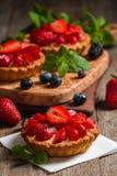 Fresh homemade berrie tarts. Fresh homemade strawberries tarts on wooden background royalty free stock photos