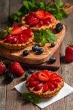 Fresh homemade berrie tarts. Fresh homemade strawberries tarts on wooden background stock photo