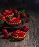 Fresh homemade berrie tarts. Fresh homemade strawberries tarts on wooden background royalty free stock photography