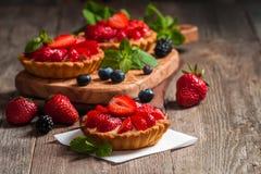 Fresh homemade berrie tarts. Fresh homemade strawberries tarts on wooden background stock photos
